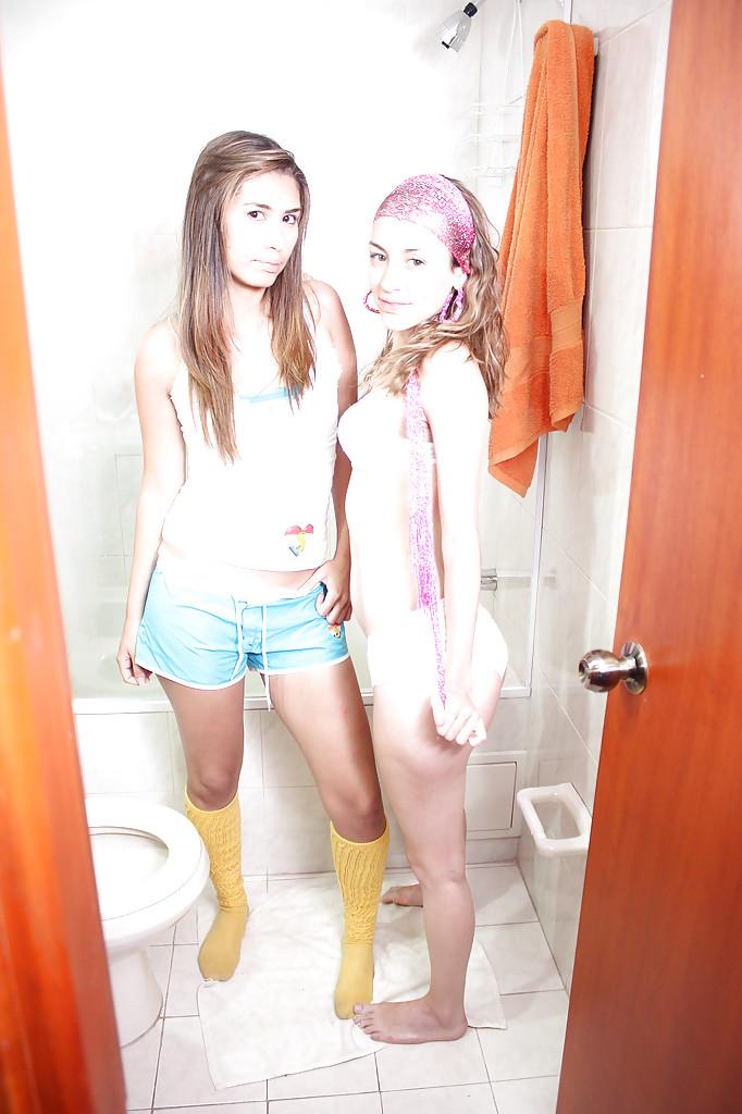 Две подружки позируют в ванной комнате